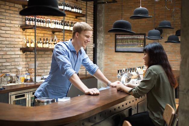 Smiling bartender talking to customer at counter