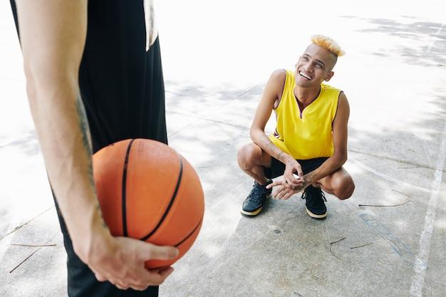 彼のチームメイトを見て笑顔のバスケットボール選手