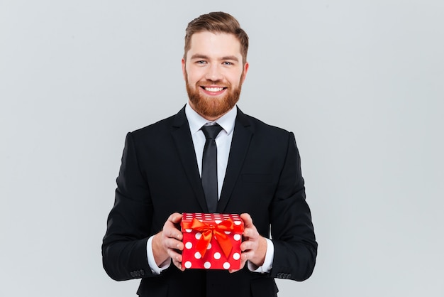 Smiling bearded business man in black suit holding gift in hands