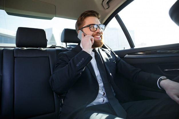 Smiling bearded business man in eyeglasses talking on cell phone