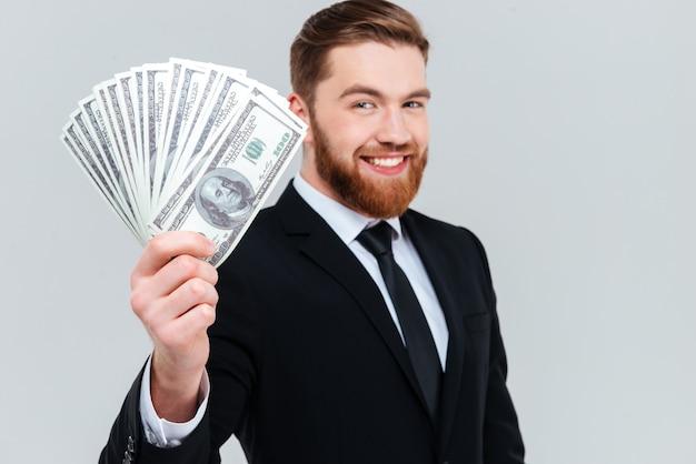 검은 양복을 입은 수염 난 사업가가 돈을 손에 들고 카메라를 쳐다보며 웃고 있습니다. 격리 된 회색 배경