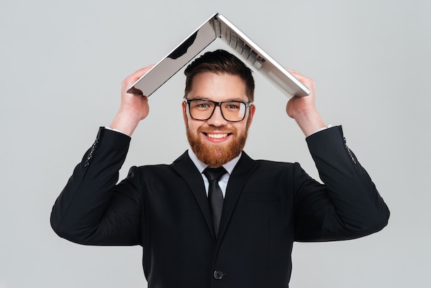 안경을 쓰고 머리 위로 노트북을 들고 있는 수염 난 사업가 웃고