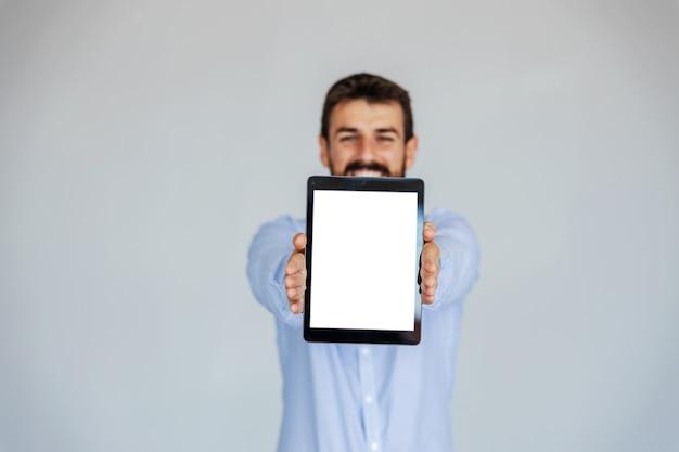 白い背景の前に立ってタブレットを保持しているひげを生やしたビジネスマンを笑顔。タブレットに選択的に焦点を当てます。