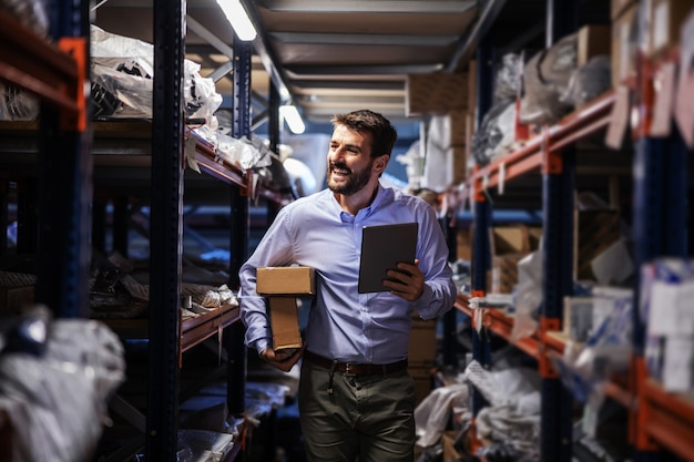 Smiling bearded businessman walking trough storage of shipping firm, holding boxes under armpit and using tablet to check on goods.