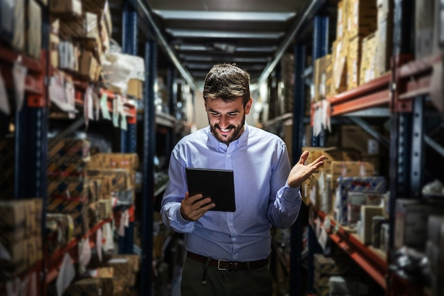 Smiling bearded chief standing in warehouse and holding tablet