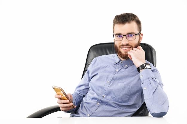 Улыбающийся бородатый элегантный мужчина в очках смотрит сидя за столом со смартфоном