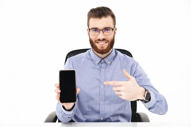 Улыбающийся бородатый элегантный мужчина в очках показывает пустой экран смартфона и указывает на него, сидя за столом