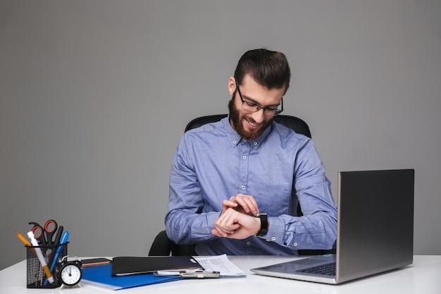 Улыбающийся бородатый элегантный мужчина в очках, используя свои наручные часы, сидя за столом в офисе