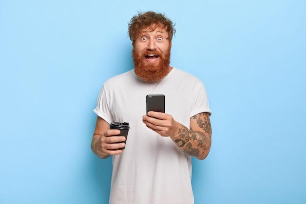 笑顔のひげを生やした感情的な男は赤い髪をして、携帯電話を持って、友人と素晴らしいニュースを共有し、広い笑顔とバグのある目で見つめ、カジュアルな白いtシャツを着て、持ち帰り用のコーヒーを持っています