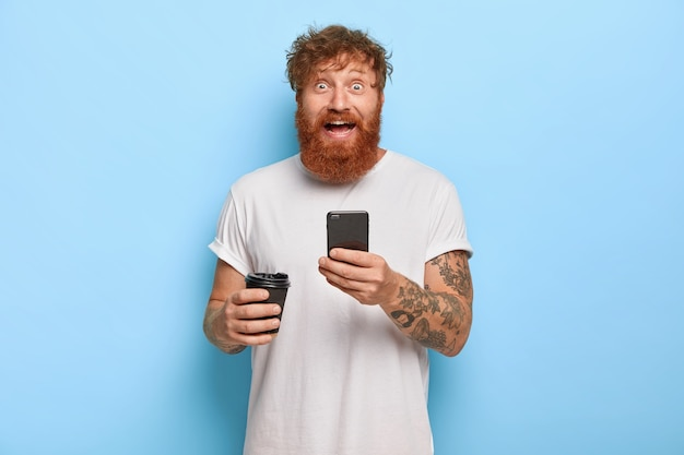 Smiling bearded emotional man has red hair, holds mobile phone, shares great news with friend, gazes with broad smile and bugged eyes, wears casual white t shirt, holds takeaway coffee