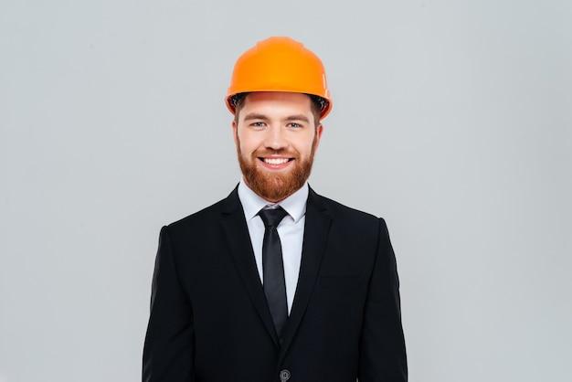 Smiling bearded engineer in black suit and yellow helmet