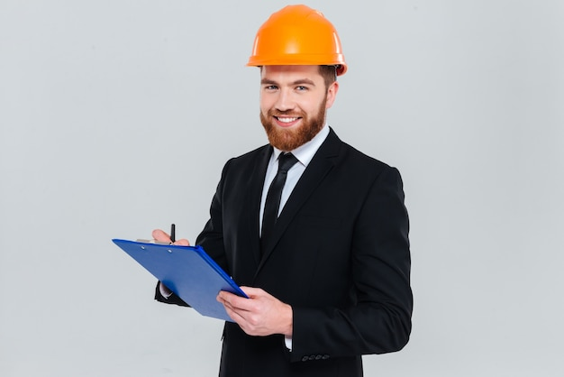 Smiling bearded engineer in suit and helmet holding clipboard