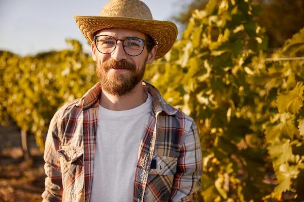 Smiling bearded farmer standing in vineyard