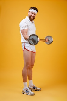 Smiling bearded fitnes man doing workout with barbell
