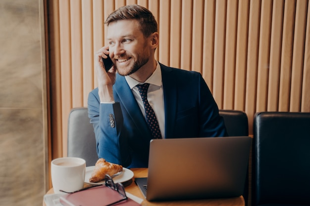 Smiling bearded handsome businessman in formal suit talking by cellphone while sitting with laptop at table in cafeteria having coffee break with cappuccino and croissant. remote work indoor concept