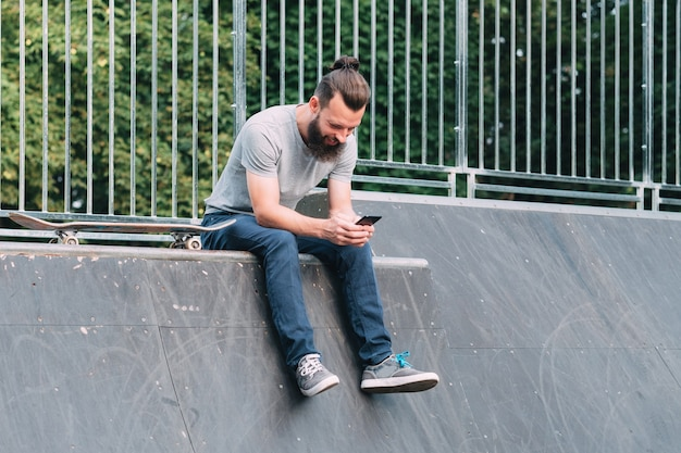 Smiling bearded hipster sitting on ramp with skateboard and browsing smartphone.