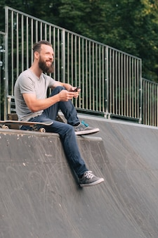 Smiling bearded hipster sitting on ramp with skateboard and smartphone.