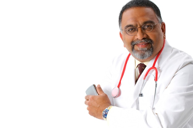 Smiling, bearded indian doctor in lab coat and stethoscope holding cell phone