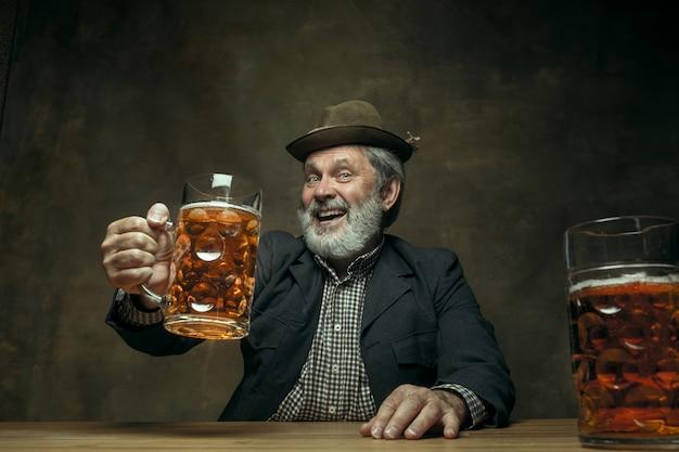 Улыбающийся бородатый мужчина пьет пиво в пабе