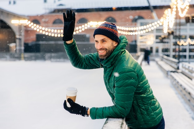 Smiling bearded male drinks takeaway coffee, waves with hand to his friend, has cheerful expression
