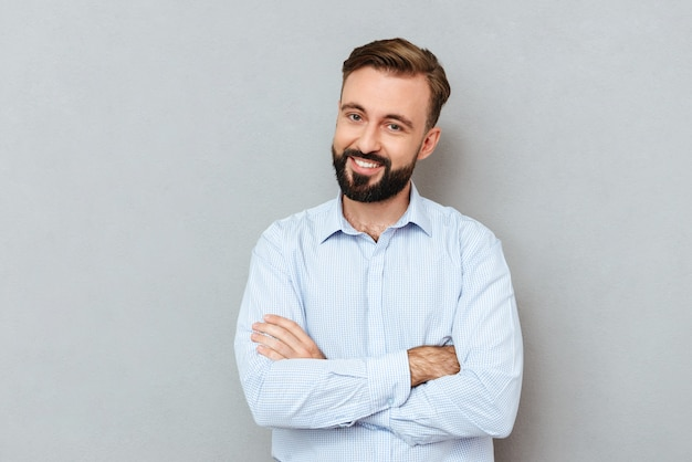 Smiling bearded man in business clothes with crossed arms