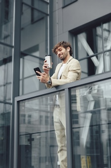 Smiling bearded man in business suit holding coffee-to-go and talking with colleagues through video call