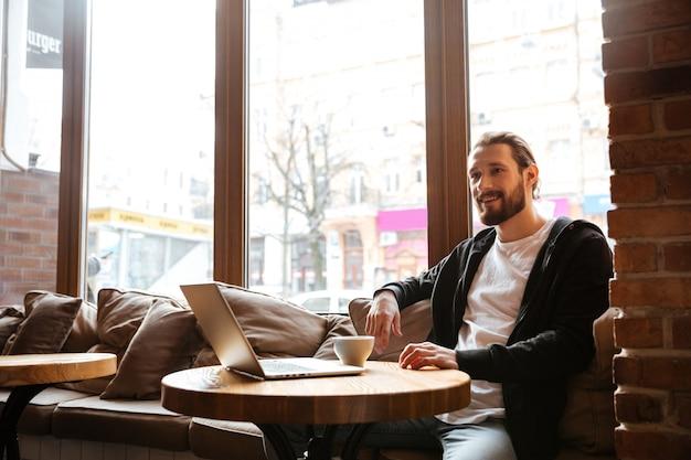 Uomo barbuto sorridente dalla tavola con il computer portatile