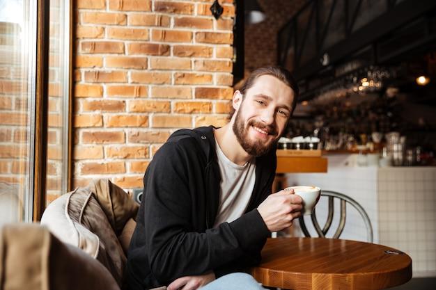 Uomo barbuto sorridente in caffè