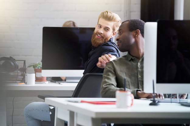 Улыбающийся бородатый мужчина привлекает внимание своего коллеги-мужчины