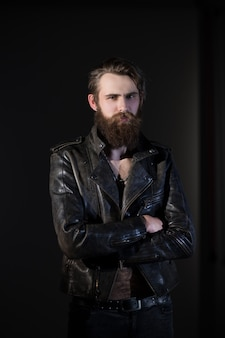 Smiling bearded man hipster in leather jacket .isolated on black background