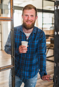 Smiling bearded man holding disposable coffee cup while opening door