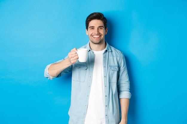 파란색 배경에 서서 머그잔을 들고 커피를 마시는 수염난 남자가 웃고 있습니다.