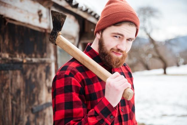 Улыбающийся бородатый мужчина в клетчатой рубашке и шляпе держит топор