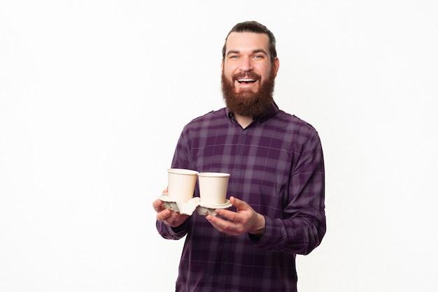 커피 두 종이 컵을 들고 체크 무늬 셔츠에 수염 난된 남자를 웃고