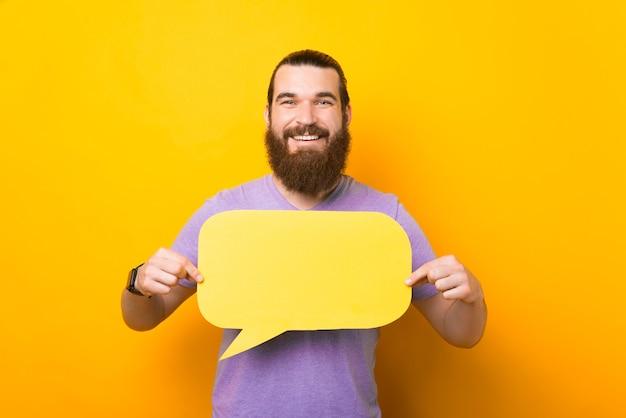 Улыбающийся бородатый мужчина держит пустой речевой пузырь с пространством для вашего текста.