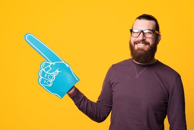 Улыбающийся бородатый мужчина держит веерную перчатку, указывая в сторону, в очках