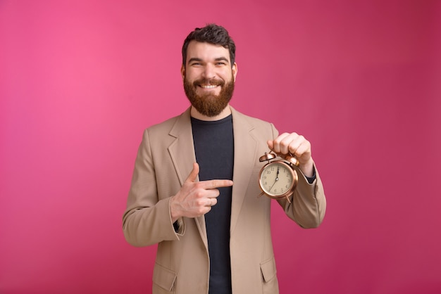 Smiling bearded man is holding an alarm clock and pointing at it.