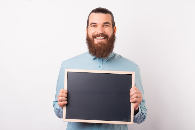 Smiling bearded man is holding a black chalkboard in front of him.