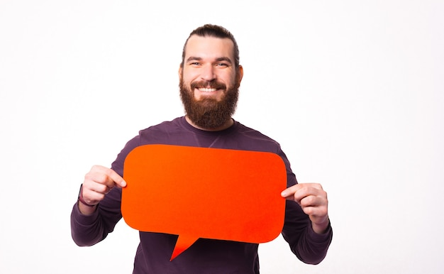 Smiling bearded man is holding a speech bubble