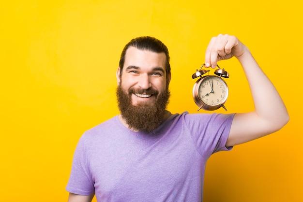 笑顔のひげを生やした男は、黄色の背景の上に目覚まし時計を保持しています。