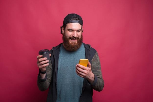 ピンクの背景の上に紙コップをかざしながら、ひげを生やした男の笑みを浮かべて彼の電話を見ています。