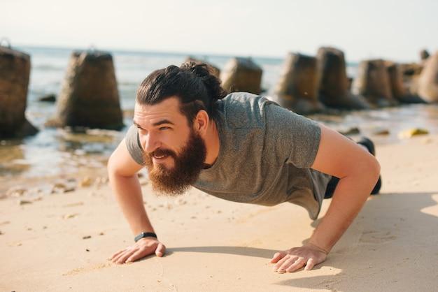 笑顔のあごひげを生やした男がビーチで腕立て伏せをしています。