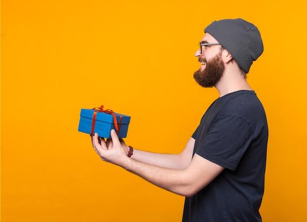웃는 턱수염이 난 남자는 노란색 벽에 선물을 제공합니다