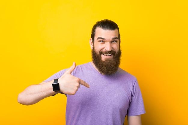 웃는 수염 난 남자가 노란색 배경 위에 자신을 가리키고 있습니다.