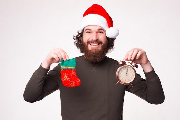 수염을 기른 웃고 있는 남자가 크리스마스 모자를 쓰고 알람 시계와 선물용 양말을 들고 있습니다.