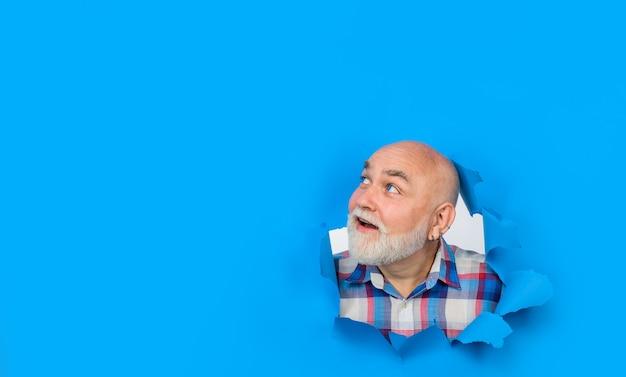紙の穴から見ているあごひげを生やした笑顔広告割引セールのコピースペース