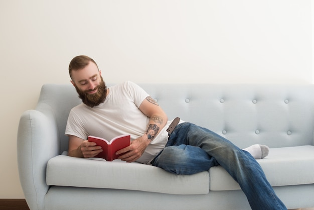 Smiling bearded man lying on sofa and reading book