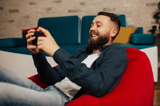 Smiling bearded man sit on the red armchair in the living room and relax at home with smartphone in hands.