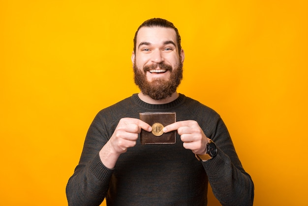 Улыбающийся бородатый мужчина стоит над желтой стеной и показывает биткойн возле кошелька