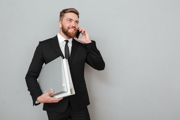 Smiling bearded man in suit talking on the phone